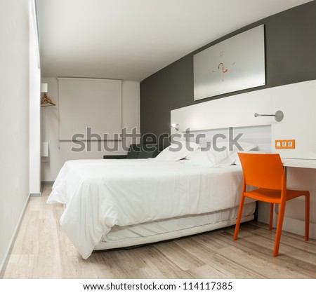 Beautiful stylish interior in modern style. Elegant design of furniture. Clean empty hotel room with double bed. Contrast of pastel colors and bright details. Night with closed window and light on.