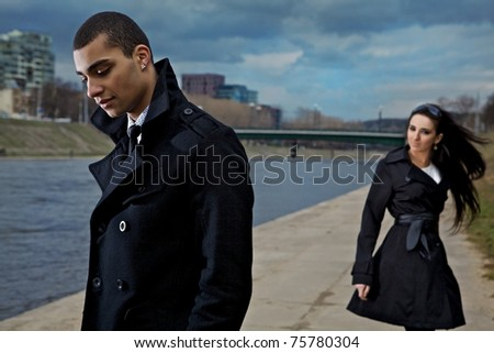 Beautiful stylish pair of young people outdoor going in different directions. Close-up men face.