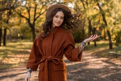 beautiful stylish smiling skinny woman with curly hair walking in park dressed in warm brown coat, autumn trendy fashion street style, wearing hat
