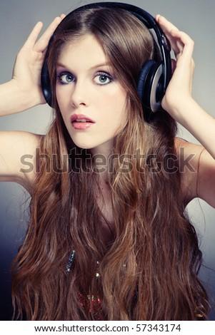 Beautiful stylish teen girl in headphones listening music