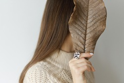 Beautiful stylish woman hiding face with big brown leaf with hand with modern round ring. Fashionable female in sweater with unusual fused glass accessories. Creative image. Beauty and care