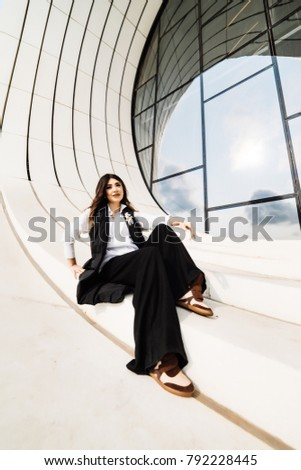 beautiful stylish woman in a black suit posing against the background of the unusual architecture of the city of Baku
