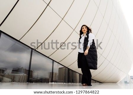 beautiful stylish woman in a business suit on a building background