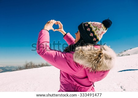 Beautiful stylish woman in snowy mountains, cute girl  of high mountain covered with snow, winter vacation concept