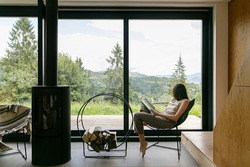 Beautiful stylish woman reading book on chair at fireplace with firewood on background of mountain hills. Young female in casual clothes relaxing in modern chalet with amazing view from window