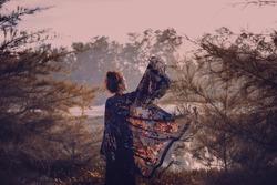 beautiful stylish woman silhouette wearing cape on sunset