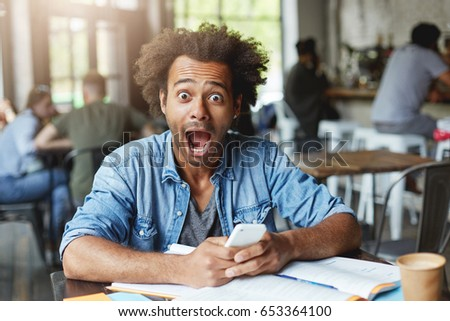 Beautiful stylish young African male student having surprised expression after recieving message looking with big opened eyes and mouth in camera being happy to pass exam. Suddenness concept #653364100