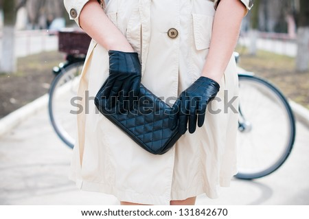 Beautiful stylish young European girl in a beige coat and a black hat and gloves with a city bicycle on a street