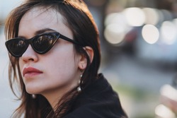 Beautiful stylish young girl model at cateye sunglasses walks around the city and poses