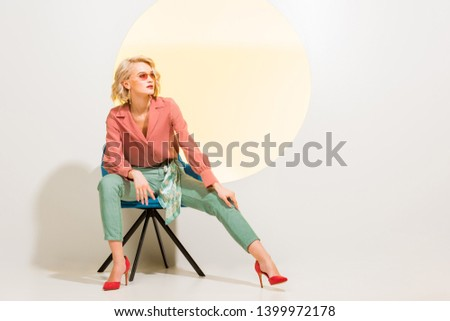 beautiful stylish young woman in colorful clothes sitting in armchair on white with yellow circle