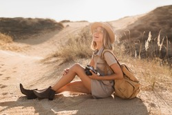 beautiful stylish young woman in khaki dress in desert traveling in Africa on safari wearing hat and backpack taking photo on vintage camera, exploring nature, hot summer, traveler on vacation