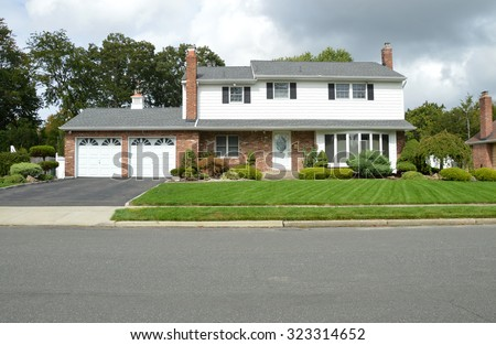 Beautiful Suburban High Ranch Two Car Garage Home Overcast Sunny Day Front yard Residential Neighborhood USA
