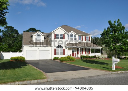 Beautiful Suburban Home Two Car Garage Aluminum Siding Blacktop driveway curbside mailbox in residential neighborhood