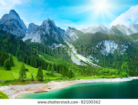 Beautiful summer Alpine mountain lake Gosausee view and sunshine in sky. Austria Alps. Beautiful natural vacation hiking walking travel to nature destinations concept.