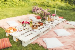Beautiful summer celebration picnic in the garden with tasty food, cold drinks. Pallet table, Flowers decoration. Pleasure time with friends. Leisure and fun. White and pink colors