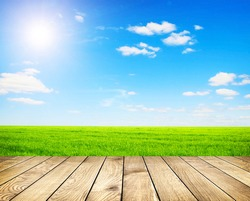 Beautiful summer green field with blue sky with grey clouds and bright sun and wooden planks on floor