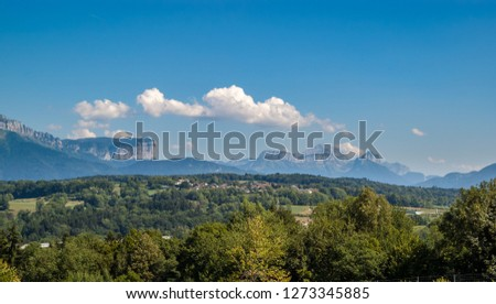 Beautiful summer panorama of the French Alps and a green hill with a village in the Auvergne Rhone Alps region.