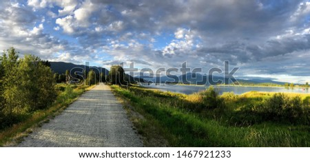 Beautiful summer panoramic view with road, mountains and river. Traboulay PoCo Trail, a 25.3 kilometre route that encircles the community. Port Coquitlam, BC, Canada.  Foto stock ©