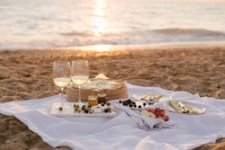 Beautiful summer picnic at sunset on beach with white wine, pizza, cheese, olives and fresh fruits.