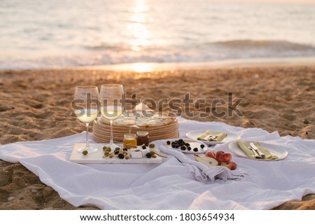 Beautiful summer picnic at sunset on beach with white wine, pizza, cheese, olives and fresh fruits. Stok fotoğraf ©
