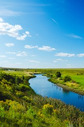 Beautiful summer rural nature landscape. Sunny view of blue river and green meadows with trees on a background. River Upa in Tula region in Russia. Summer background. Beauty of summer nature.