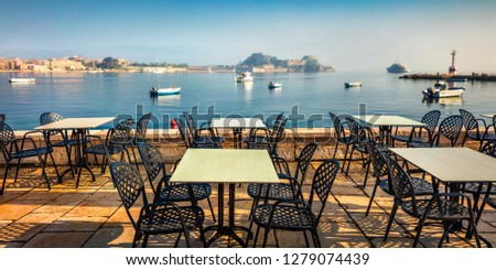 Beautiful summer seascape of Ionian Sea, Corfu island, Greece, Europe. Panoramic morning view of cozy seaside restaurant with old Venetian fortress in Kerkira town on background.