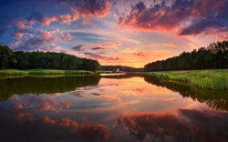Beautiful summer sunset at the river with blue sky, red and orange clouds, green trees and water with reflection  (Ukraine)