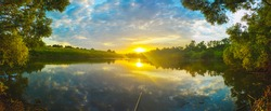 Beautiful summer sunset nature landscape. Tranquil evening scene with warm sunlight and amazing reflection of clods in sky on the water surface. Calm lake and green hills at sunset.Fishing time.
