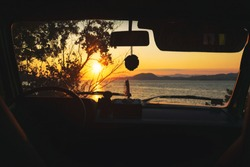 Beautiful summer sunset view through the windshield of old timer classic camper van parked on the beach near the sea shore. Vintage summer warm background - Image