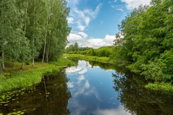 Beautiful summer view of a calm river with lush green trees along the riverbank and the blue sky reflecting in the dark water