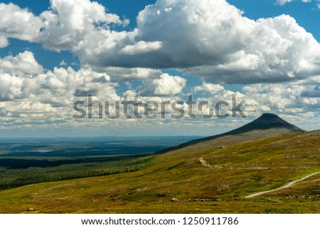 Beautiful summer view over the northern Swedish mountains or fjeld word in Northern Sweden with blue sky and fluffy white clouds