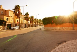 Beautiful sun downer with palm streets next to the street with a parked car