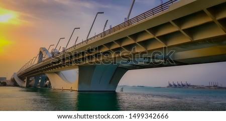 beautiful sun set and bridge in abu dhabi and oil factory behind.