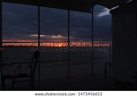 Beautiful sundown view from an old ship. The darkness going to ashore, dramatic cloudy sky with a thin line of sunset light over sea. Twilight on the coast, calm evening. Romantic boat trip. Sea cafe #1473456653