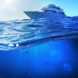 beautiful sunlight seaview safari dive boat in tropical sea with deep blue underneath splitted by waterline. Design template