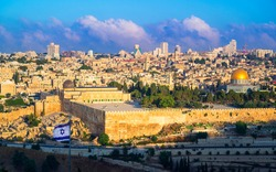 Beautiful sunlit view of Jerusalem: the Temple Mount with Dome of the Rock and Al Aqsa Mosque, archaeological park of the Southern Wall and Huldah Gates; with Israeli flag in the foreground and clouds