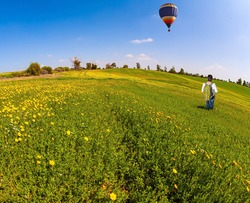 Beautiful sunny day in April. Woman is walking in a grassy field. Bright multicolor hot air balloon flies over the field. Photo taken with fisheye lens. Israel.