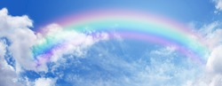 Beautiful sunny summer blue sky panoramic rainbow - fluffy clouds with a giant arcing rainbow against a beautiful summertime blue sky with plenty of space for text