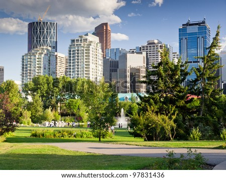 Beautiful sunny summer day in Calgary Downtown. Beautiful view of downtown of the biggest Alberta city - Calgary. Image taken from Prince's Island park with it's fountains and mature trees.