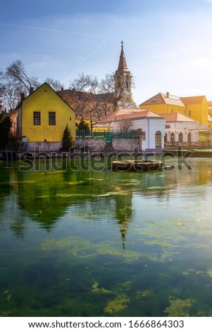 Beautiful sunny view of lake Malom with colors houses and a Roman Catholic Church in Tapolca. Reflection photo of a romantic part of the town is the Mill Pond (Malom-tó).  Stock fotó ©