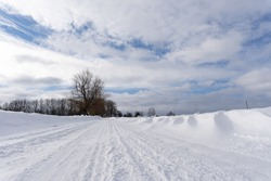 beautiful sunny winter day in Latvian countryside with blue skies and white clouds where there is a road in the middle of the field that is covered with snow and on which the tracks of car tires