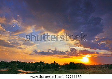 Beautiful sunrise and dramatic clouds on the sky. Flood waters of Narew river, Poland.