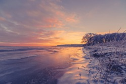 Beautiful sunrise at a frozen sea shore in Scandinavia