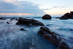 Beautiful sunrise at a rocky beach on northern coast of Taiwan, with golden sun rising on distant horizon, turbulent waves beating on rugged rocks and lights of fishing boats glowing under dawning sky