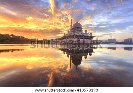 beautiful sunrise At Putra Mosque, Putrajaya Malaysia with colorful clouds and reflection on the lake surface