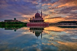 Beautiful sunrise at the majestic Putra Mosque in Putrajaya, Malaysia with colorful clouds and reflection on the lake surface.