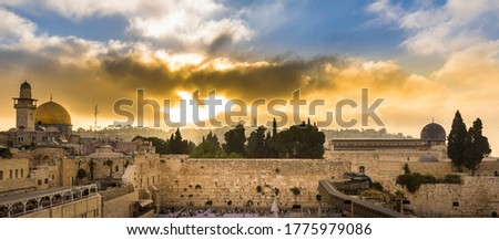 Beautiful sunrise clouds over the Mount of Olives and the Temple Mount sites: Dome of the Rock, Western Wall and Al Aqsa Mosque; with Jewish people praying in sections because of covid-19 regulations