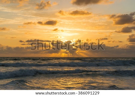 Beautiful sunrise cloudscape over ocean background. Sun rays beaming through picturesque clouds above sea