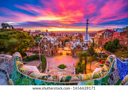 Beautiful sunrise in Barcelona seen from Park Guell. Park was built from 1900 to 1914 and was officially opened as a public park in 1926. In 1984, UNESCO declared the park a World Heritage Site