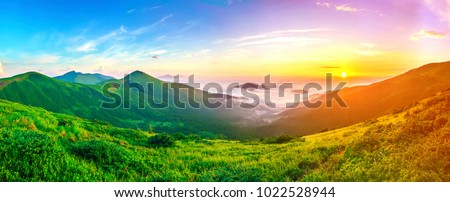 Beautiful sunrise in mountains with white fog below panorama #1022528944